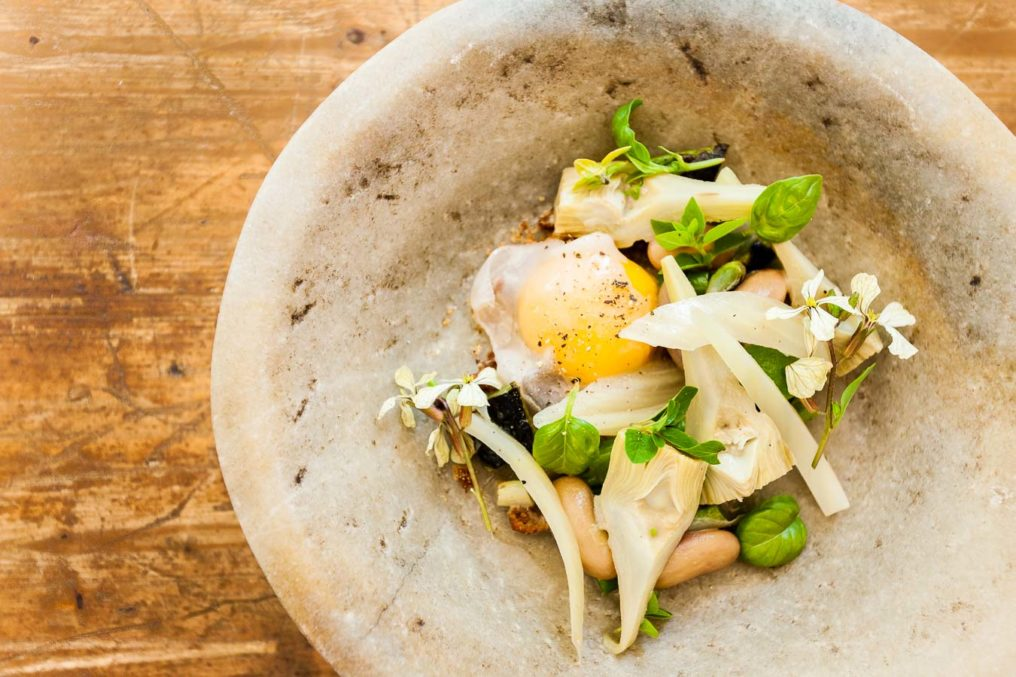A stone bowl containing cooked artichoke hearts, a duck egg, beans, edible flowers and herbs on a wooden table top, served at The Dairy restaurant