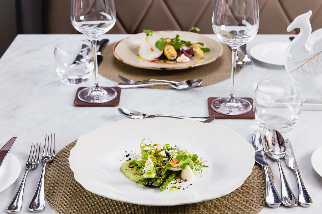 Fine dining table setting with textured place mats and two plates of carefully prepared food, polished cutlery and wine glasses