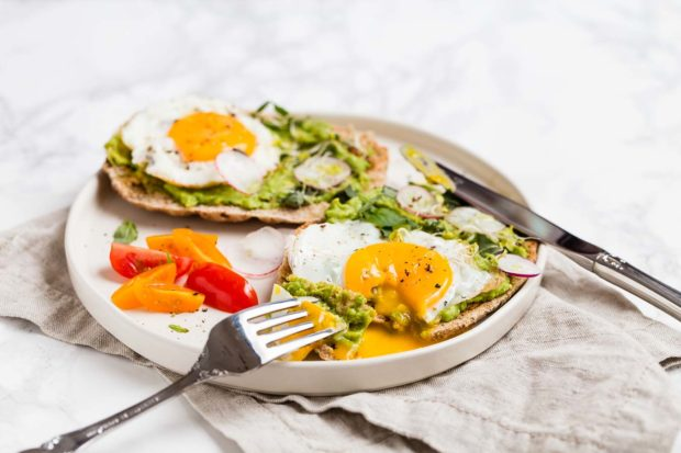 Avocado and fried egg on a thin pizza crust with thin slices of radish and sliced tomato on a shallow plate. Slice cut out of one avocado breakfast pizza with egg yoke running onto plate