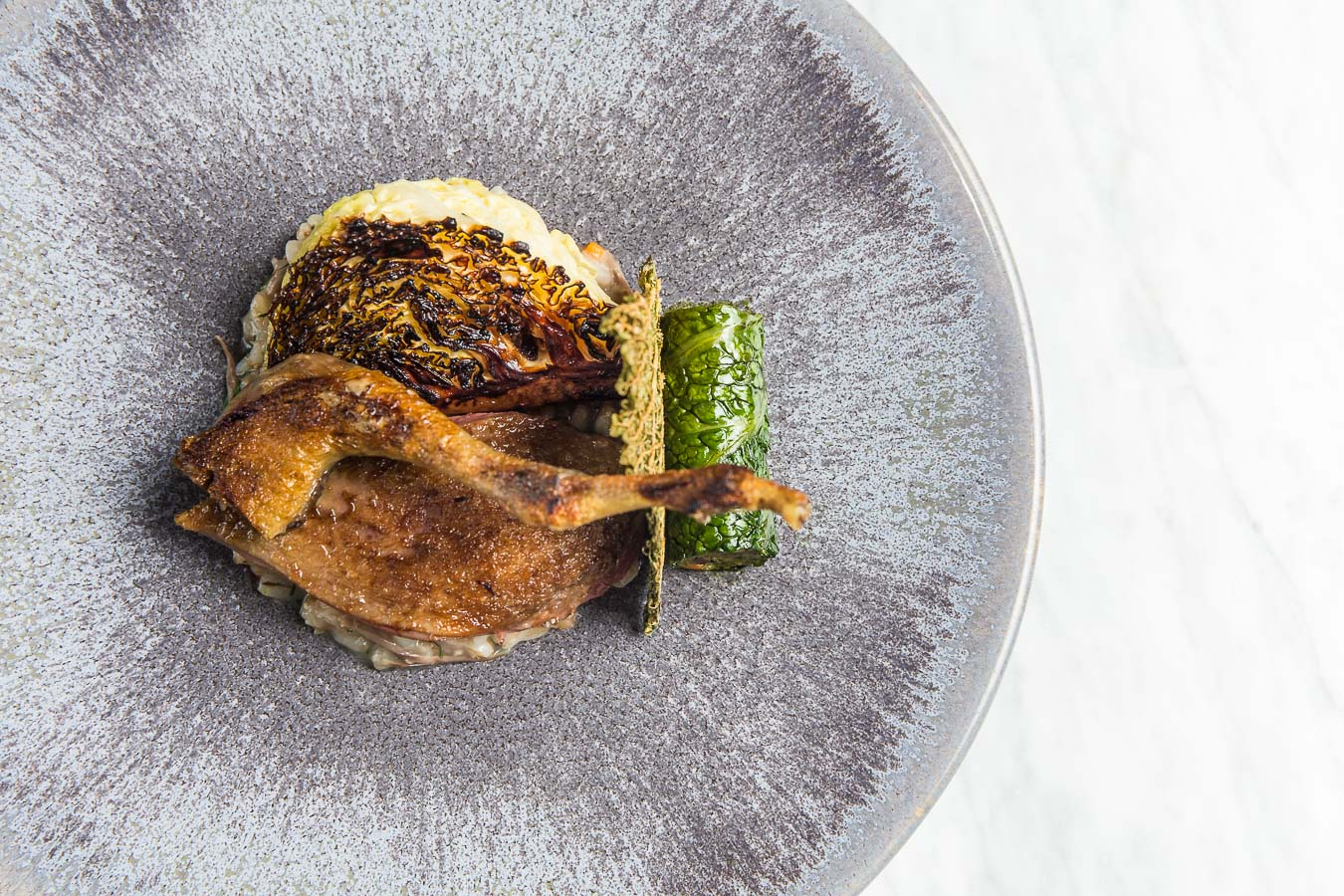 Chicken leg carefully plated in a fine dining style, with a leaf wrapped confit leg meat on a textured grey plate