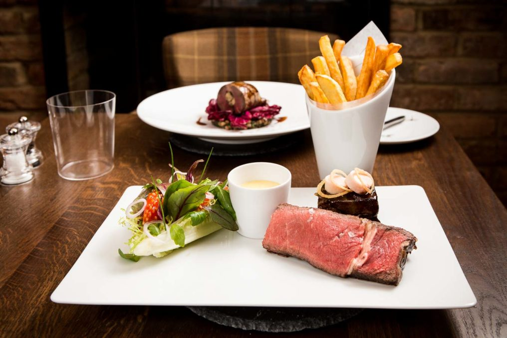 Gastro pub wooden table setting with steak, chips, a side salad carefully plated. Served at The Oxford Blue Pub, Windsor by Chef Steven Ellis