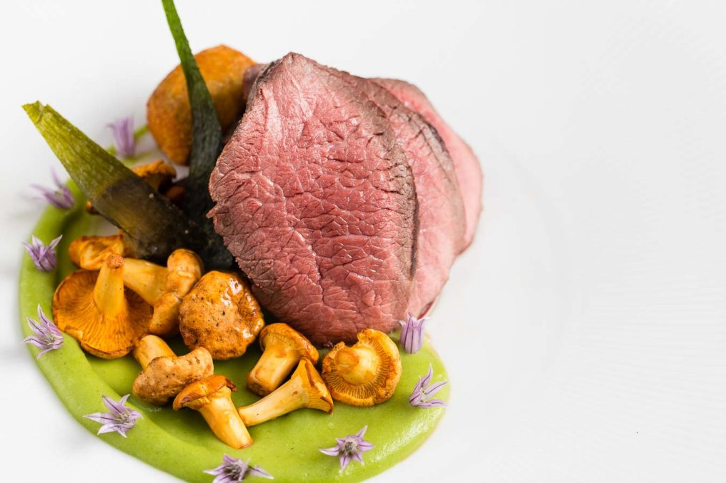 Slices or medium rare beef with a pea purée and girolle mushroom carefully plated on a white plate, from The Oxford Blue Pub by Chef Steven Ellis