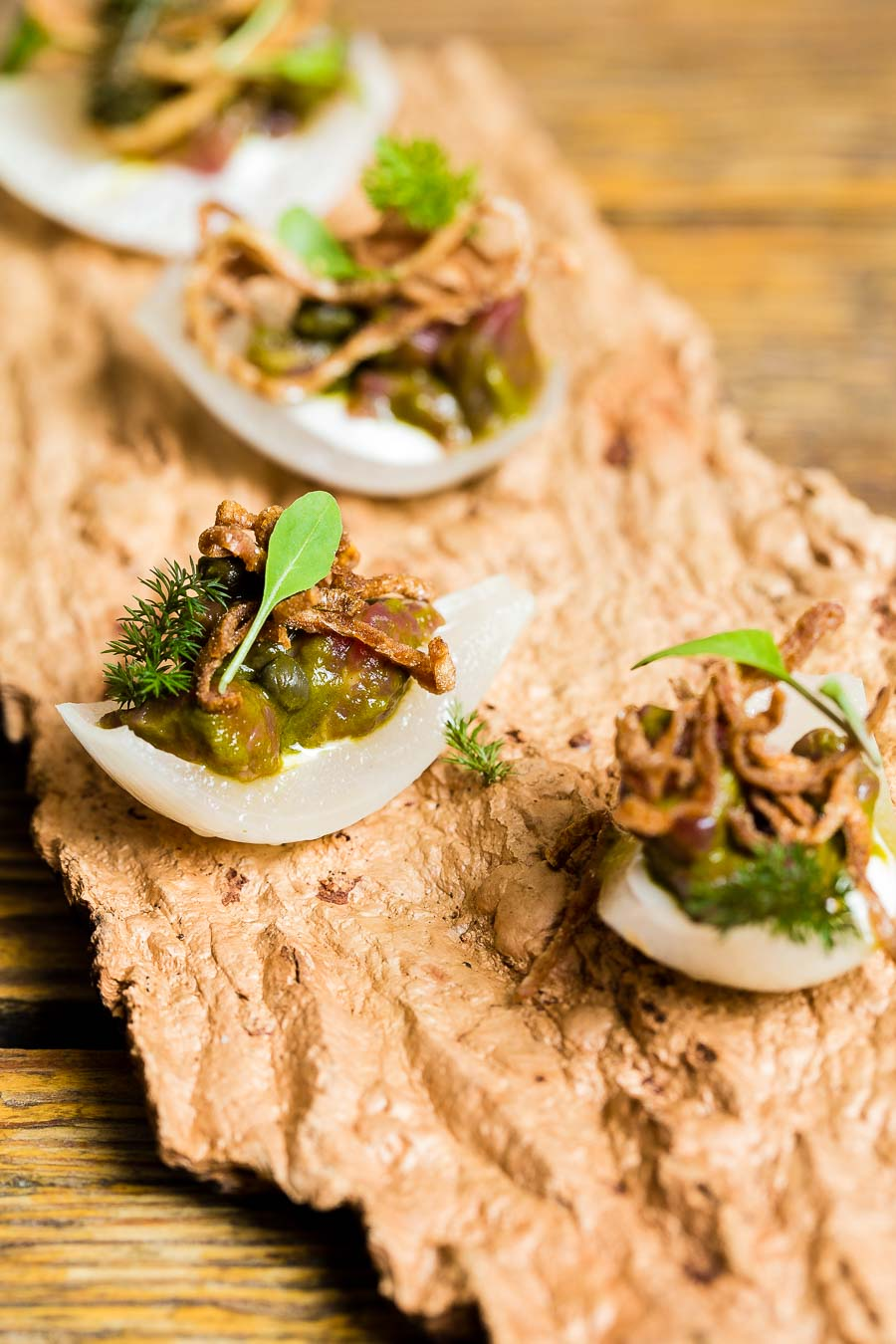 A piece of wooden bark with small slices of rock oysters topped with beef tartare and herbs, served at The Dairy from chef Robin Gill
