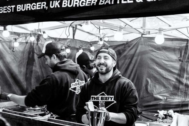 Beefy Boys serving street food. Bearded male smiles big at customers who are out of shot
