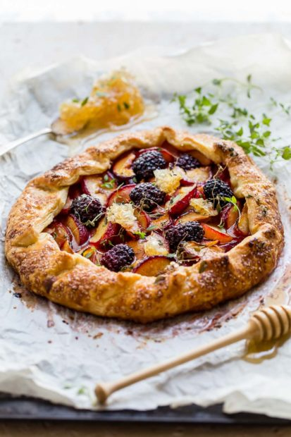 Round cornmeal pastry galette filled with roasted plums and blackberries, drizzled with honey, sitting on a greaseproof sheet with green micro herbs and honeycomb