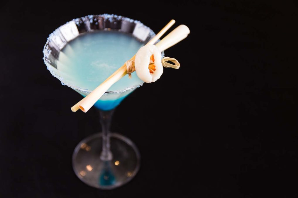 Long stem cocktail glass containing a blue drink, garnished with a shrimp on a black background