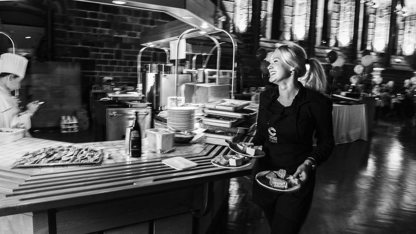 Candid environmental portrait of female server returning to the kitchen with plates of food smiling