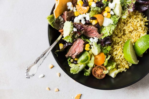 A black bowl of beef, lettuce, sweet corn, beans, sliced cherry tomatoes and crumbled cheese on a bed of rice with lime quarters making up Carne Asada