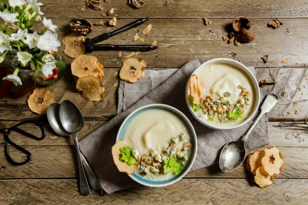 Top down view of two bowls of celeriac soup topped with walnuts and crumbled cheese with apple crisps, served on a wooden table top and linen cloth styled with spoons and a nutcracker