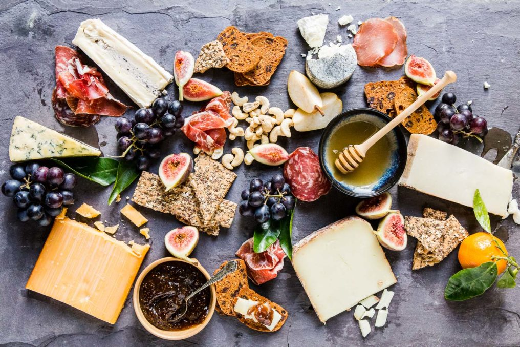 Flat lay of a six variety cheese board with charcuterie, cracker, nuts, figs, pears, grapes and two dips served on a slate surface