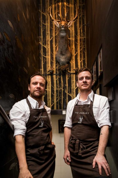 Environmental portrait of Chefs Brett Graham and Greg Austin at The Ledbury for Art Culinaire Magazine, two male chefs standing side by side in a hallway. A stuffed stags head and neck is mounted on the wall behind them.