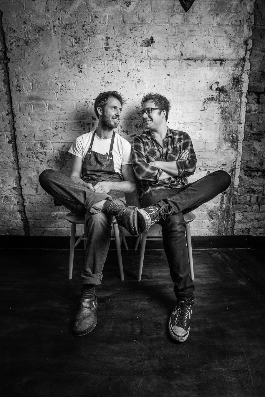 Portrait of Chef Dean Parker and Manager Dan Joines for Robin Gill. Two young men sitting on chairs looking at each other with a rustic brick background