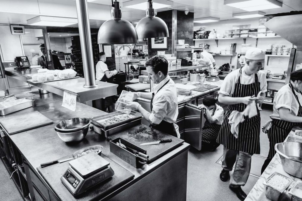 Candid back and white photo of the kitchen at The Ledbury while they prep for service, Head Chef Greg Austin in the foreground