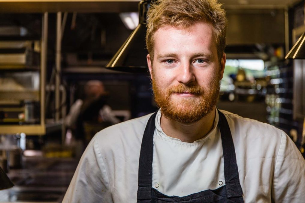 Portrait of male bearded chef with red hair in a commercial kitchen