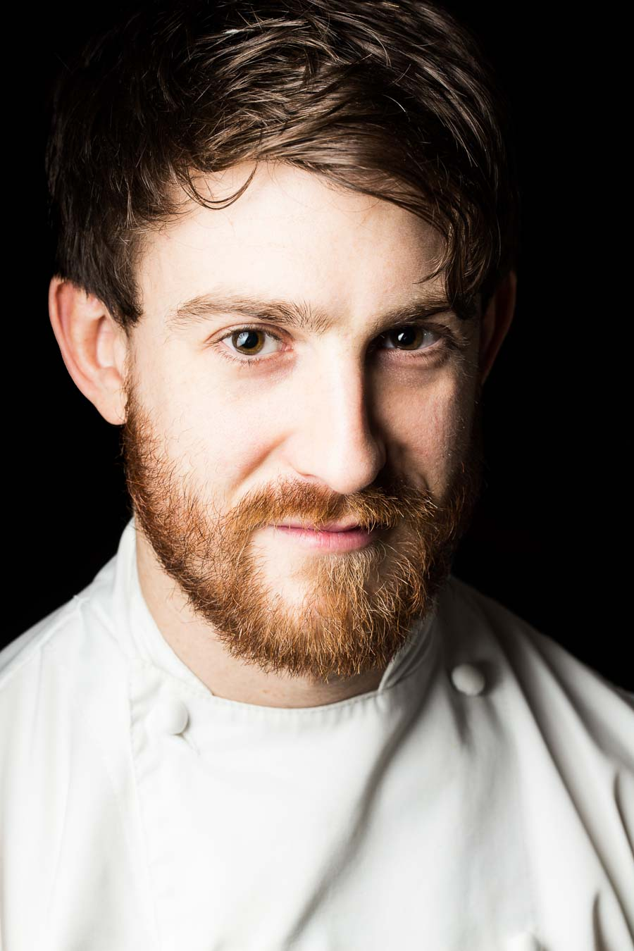 Head shot of chef Lee Westcott for Art Culinaire magazine. Chef is wearing chef whites, has a beard and the background is very dark