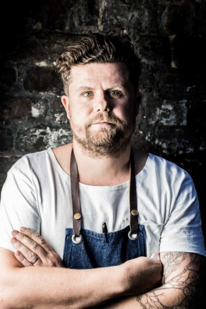 Portrait of Chef Robin Gill featured in Art Culinaire Magazine 119. Bearded male with tattoo on left arm standing in front of a rustic, brick wall, with dramatic side lighting