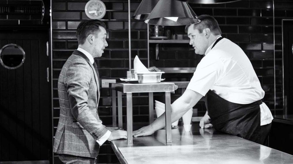 Black and white photo of chef Steven Ellis leaning across the pass and talking to Daniel Crump in the kitchen of The Oxford Blue Pub
