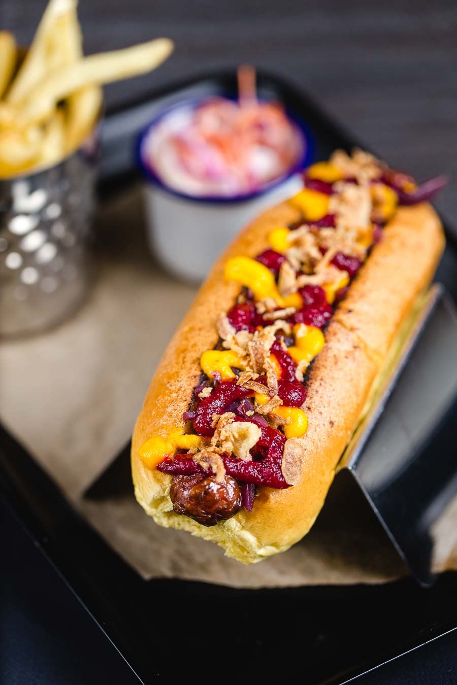 A chilli hotdog dressed with a spicy tomato ketchup, mustard and crispy onion pieces with a container of fries and tub of coleslaw in the background. Served at The Bootroom at LFC Anfield