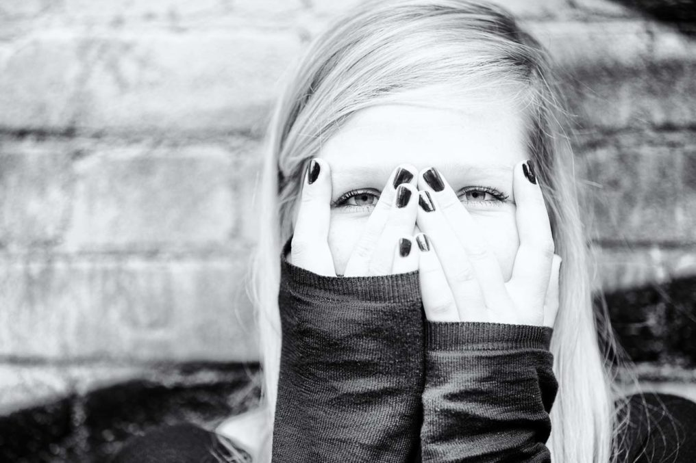 Fun portrait of Claire Wright hiding her face behind her hands and a rustic brick wall background