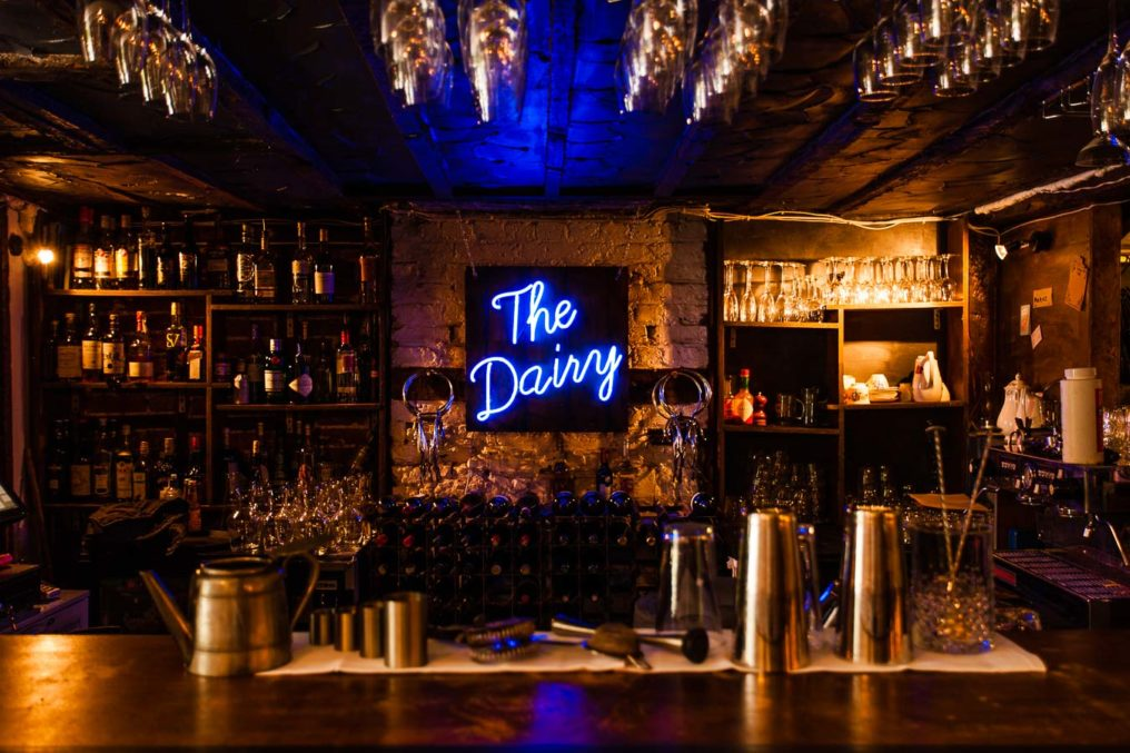 The bar at The Dairy with cocktail mixing equipment on the bar, bottles and glasses on shelves and a blue neon sign saying The Dairy