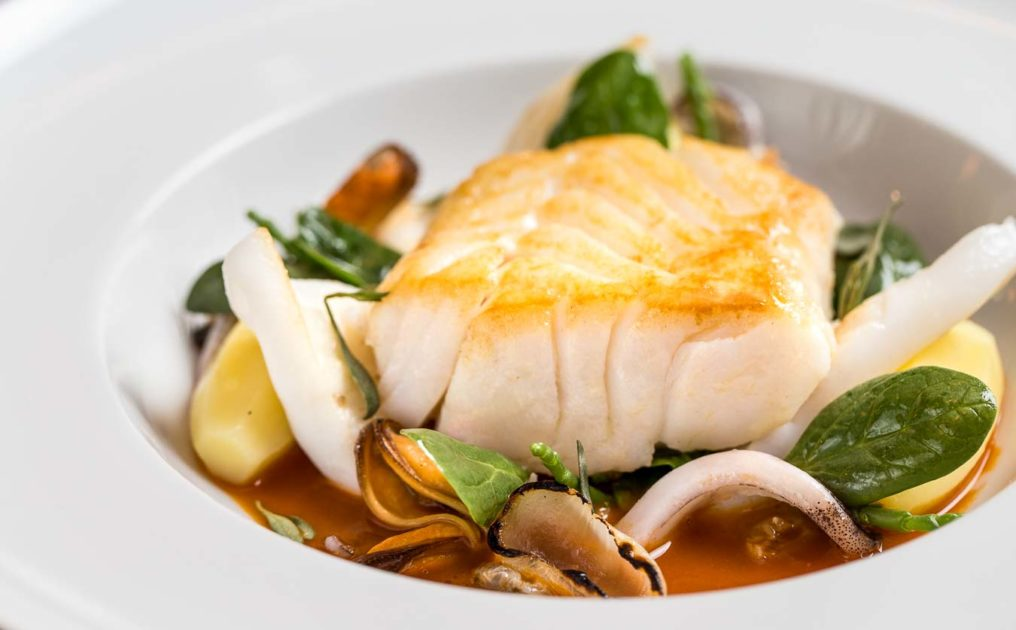 Closeup photo of cooked cod with seaweed, clams and velouté in a white bowl, served at The Oxford Blue Pub by Steven Ellis