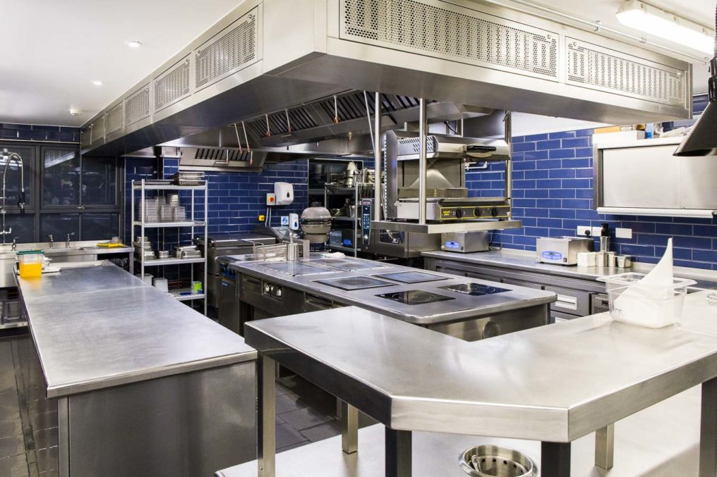 Spotlessly clean commercial kitchen with stainless steel work surfaces and blue subway tile at The Oxford Blue Pub