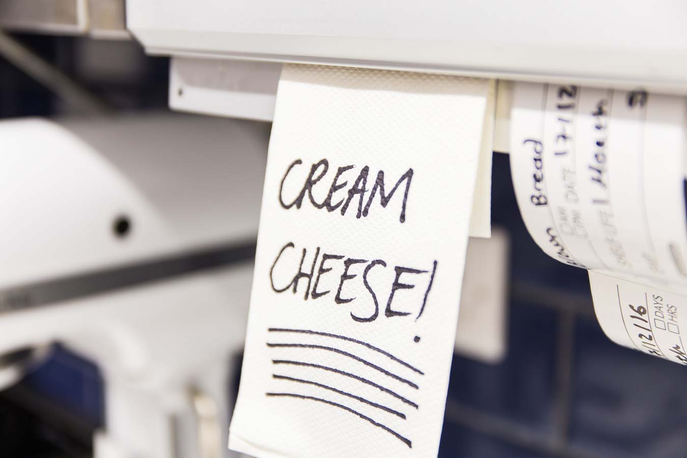 Closeup of a reminder note in a pastry kitchen with cream cheese written on it