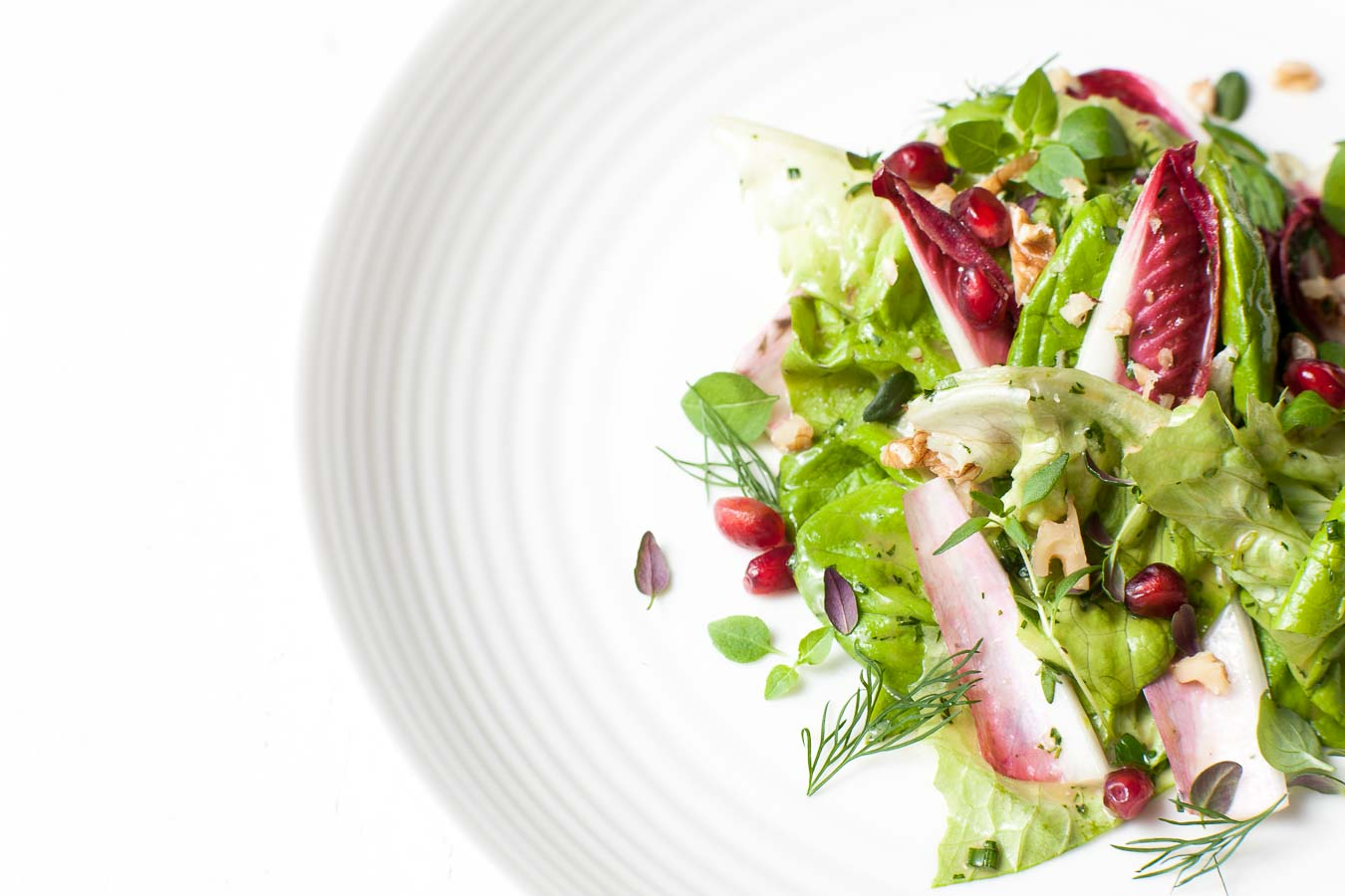 A salad with crisp lettuce, endive, herbs and pomegranate seeds, on a white plate