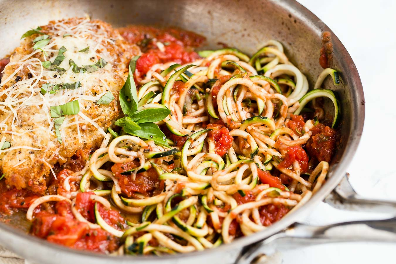 A frying pan with a cooked crispy chicken breast covered with herbs and parmesan cheese next to cooked tomatoes and zucchini noodles or zoodles