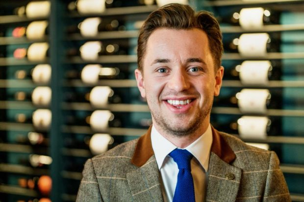 Head shot of Daniel Crump wearing a blue tie and tweed jacket with wine rack in the background at The Oxford Blue for Steven Ellis
