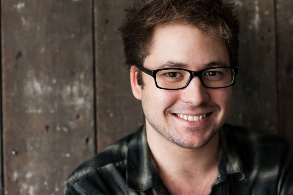 Natural light portrait of Dan Joines smiling. Young male, brown hair, wearing dark framed glasses