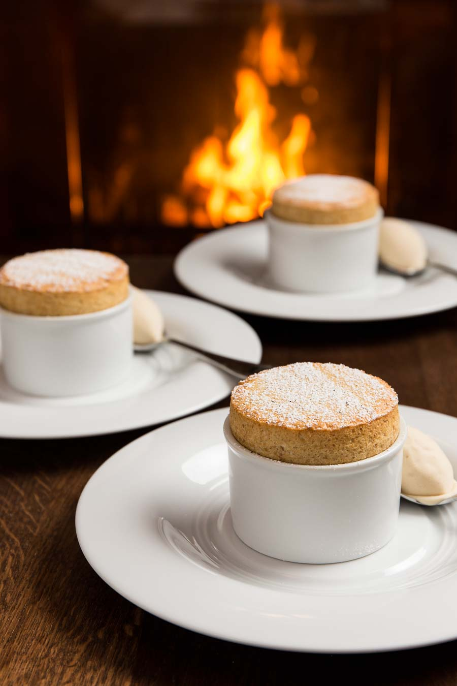 Three soufflé in white bowl, on white plates, along side spoons with quenelle ice-cream, on a wooden table with a lit fireplace in the background