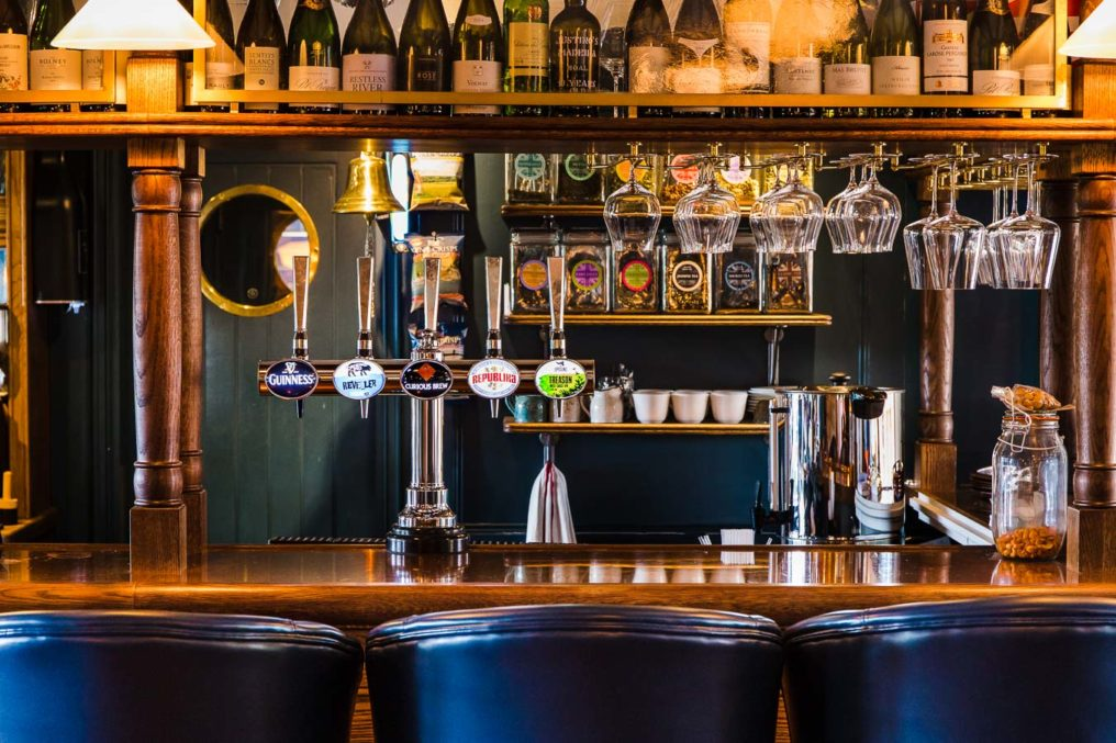 The bar at The Oxford Blue pub showing the backs of three blue stools, beer pumps, wine bottles and glasses up above the bar