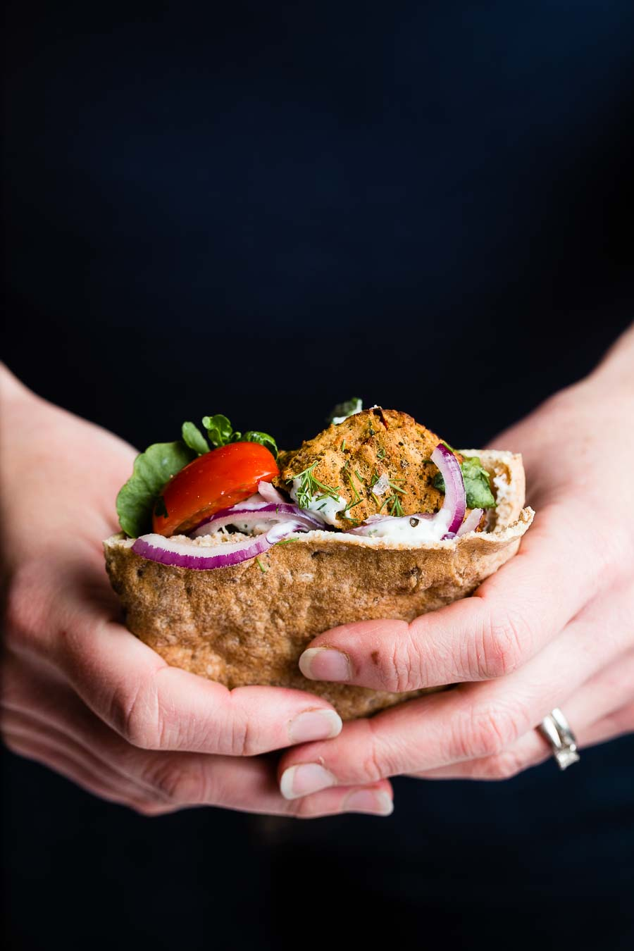 A pita pocket stuffed with cooked falafel tomato, salad, purple onion and dressing, presented by a woman's hands holding the stuffed pita with a dark blue background