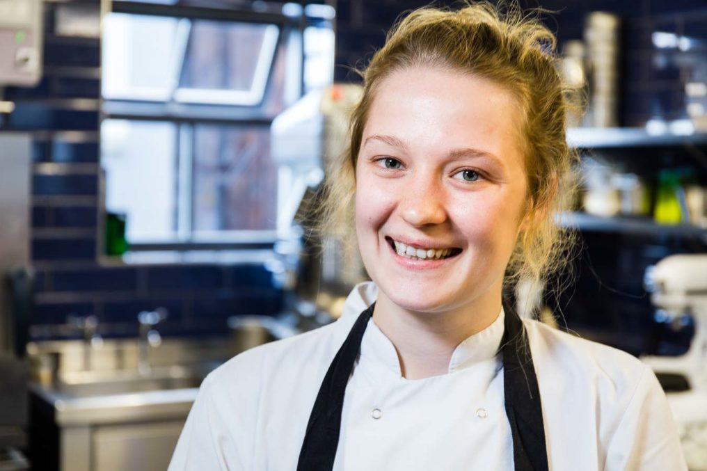 Portrait of female chef in a commercial kitchen, smiling