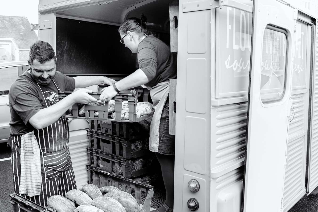 Baker at Flour Water Salt loading the Citroen H2 van with sour dough loaves of bread