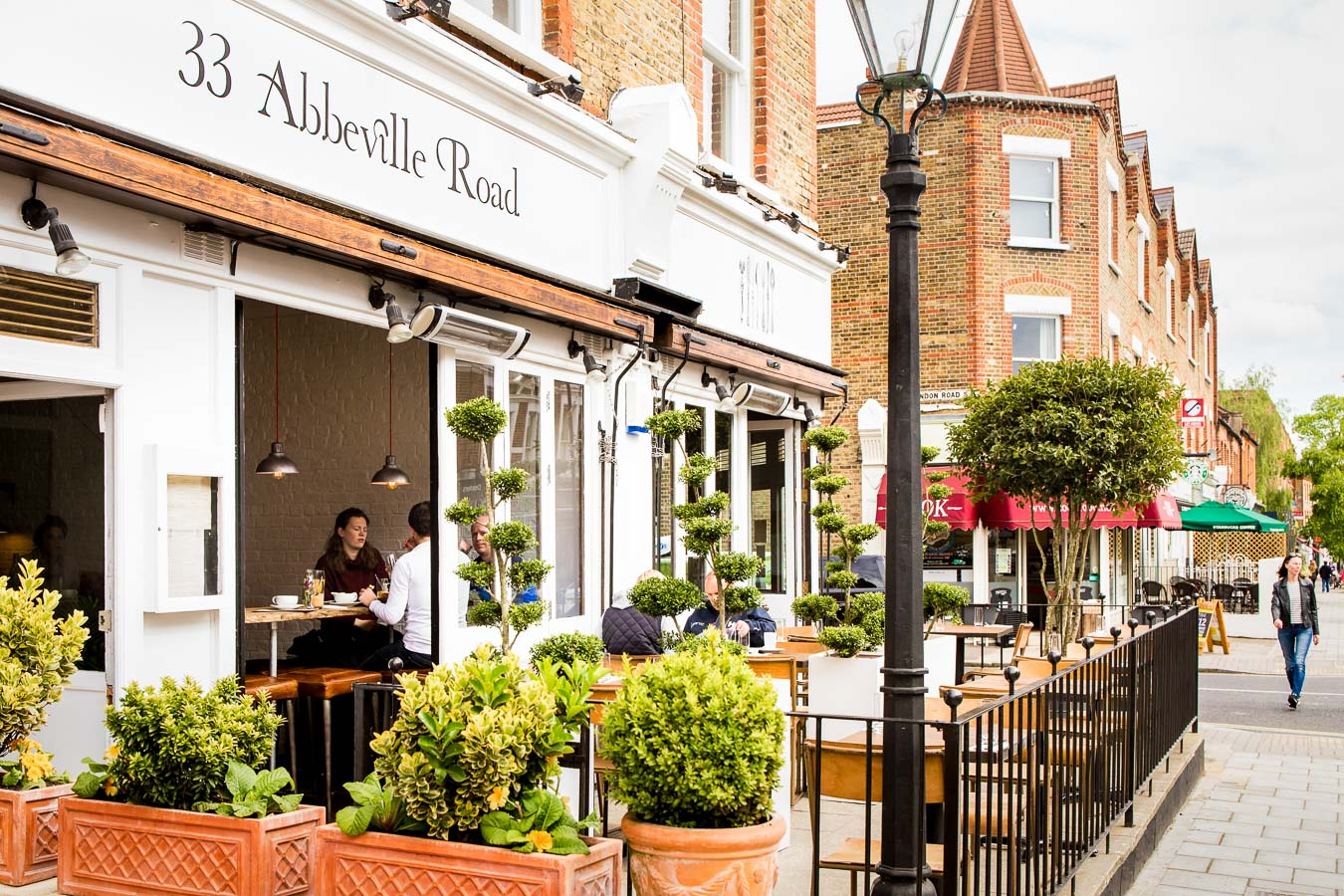 Front street scene of a bistro called 33 Abbeville Road, showing the patio and diners eating outside and inside