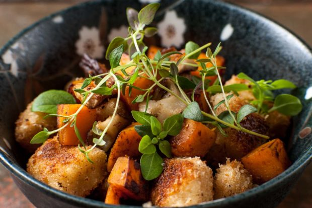 A dark and flower pattern bowl containing cooked gnocchi with roasted sweet potato garnished with fresh herbs