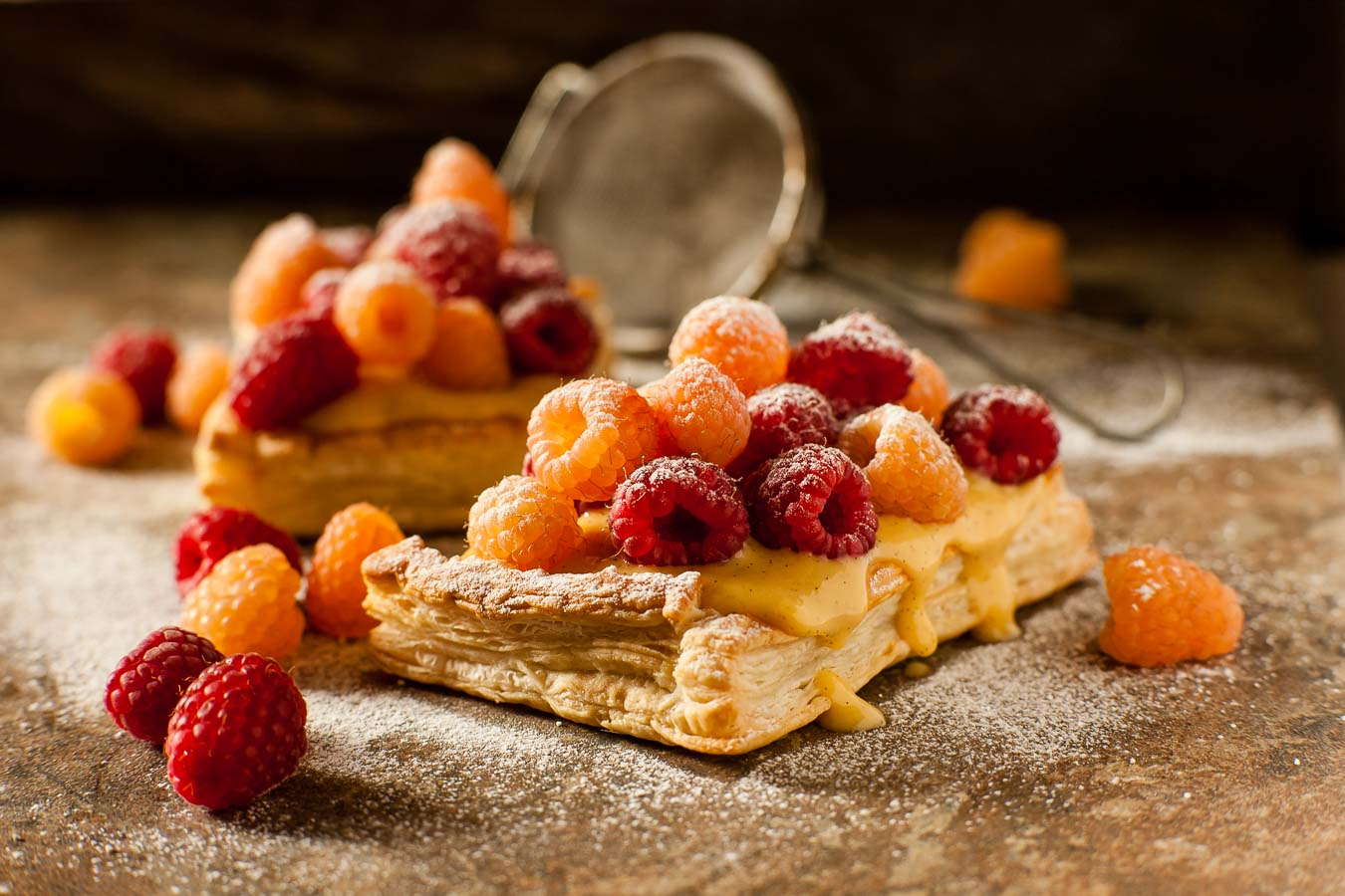 Puff pastry square topped with vanilla custard, with red and golden raspberries, dusted with icing sugar