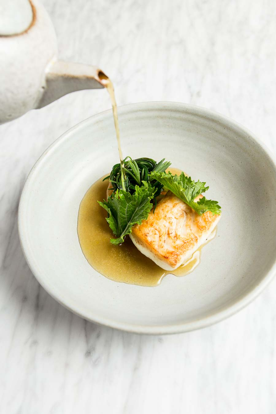 A stoneware bowl containing a fine dining dish of hake, having a gravy poured into the bowl from a stoneware teapot, at Typing Room from chef Lee Westcott