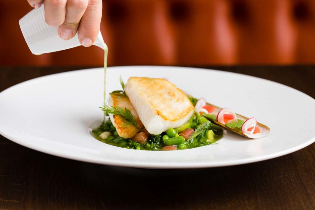 Pieces of cooked John Dory fish with a razor clam, peas and a minestrone broth being poured onto the food