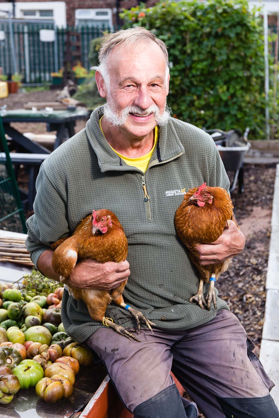 Organic gardener with handlebar mustoch in his allotment holding two chickens, one in each hand, for Liverpool Football Club