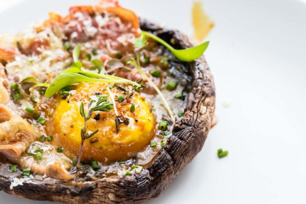 Close up photo of a baked portobello mushroom with a baked egg and pancetta with green micro herbs