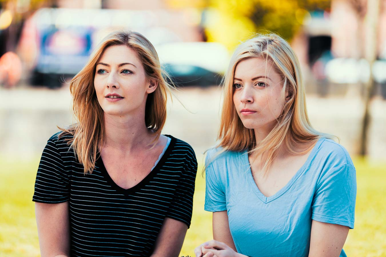 Two beautiful young women in casual clothes, with blond hair, look over to camera left with an out of focus urban background. The colours are of a cinematic quality