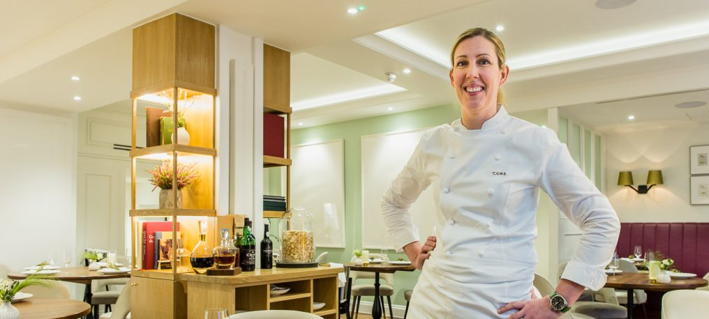 Environmental portrait of female chef, Clare Smyth, standing in the restaurant Core dining room wearing chef whites.