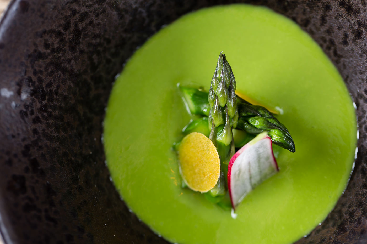 Green soup sits in a dark charcoal dappled bowl with asparagus tips and radish stacked in the centre