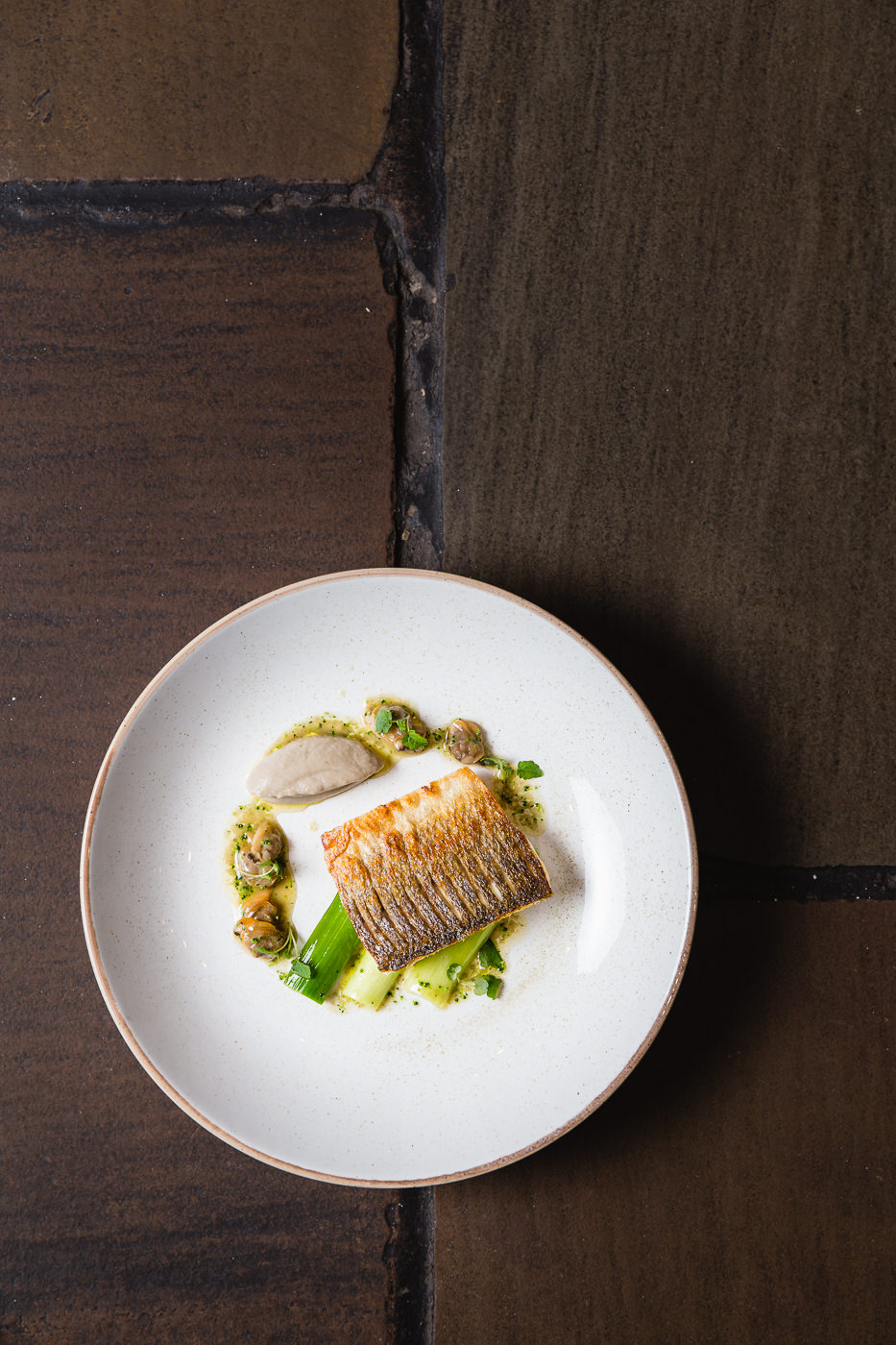 Top down shot of restaurant style cod loin sitting on leaks with mushrooms and a sauce. The white plate is on the intersection of dark, old, stone floor tiles