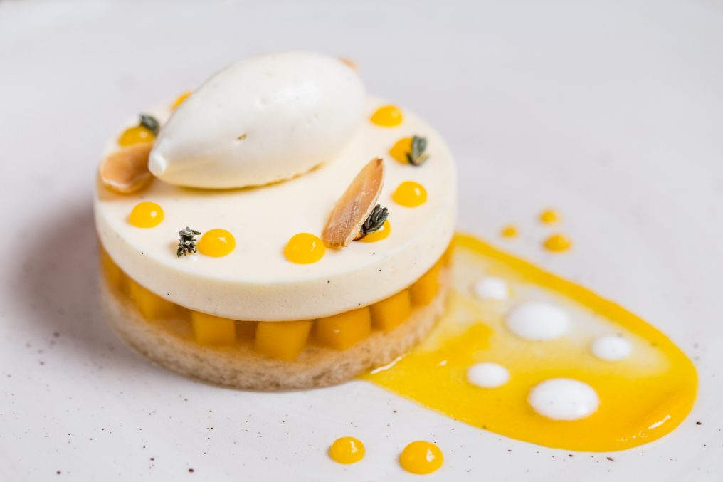 A restaurant style dessert, circular textured base with a white circular top standing on orange squares. A quenelle of white ice-cream is on top with half pine nuts and orange circular blobs. There's an orange chef sweep which everything sits on with a white plate