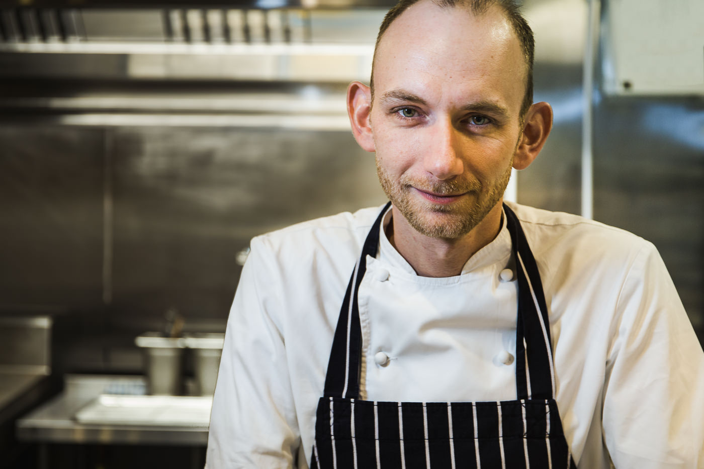Environmental portrait of chef Stuart Collins, standing in his kitchen at restaurant Docket 32, looking straight to camera in chefs whites and apron