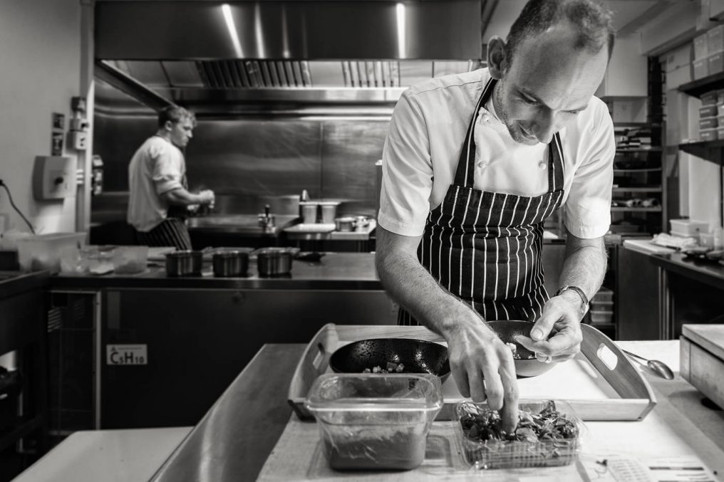 Candid black and white shot of chef Stuart Collins plating food during service, while another male chef can be sen working in the background